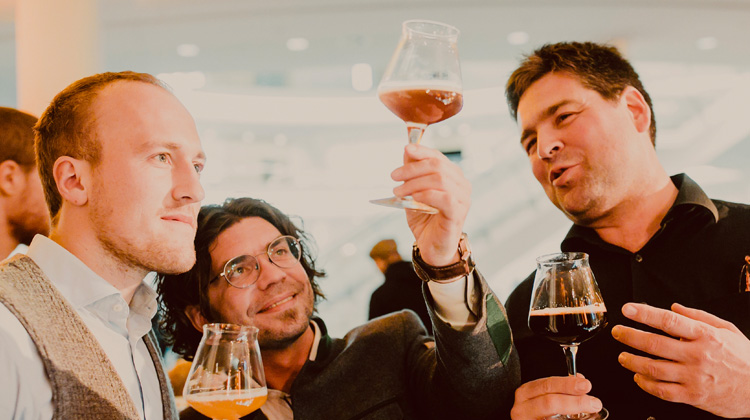 Three men during a beer tasting talk about these beers