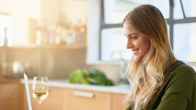 Woman sits at the kitchen table with a glass of wine and reads an article on her laptop