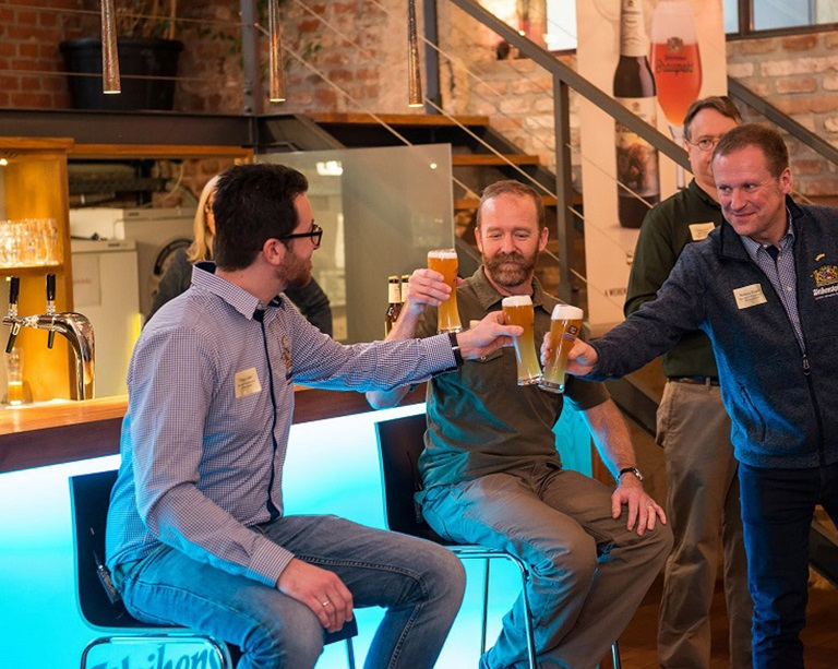 Three men are clinking with beer glasses