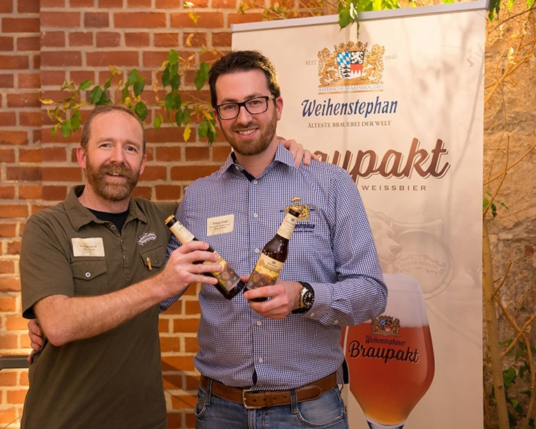 Two men are posing in front of a poster with beer in their hand