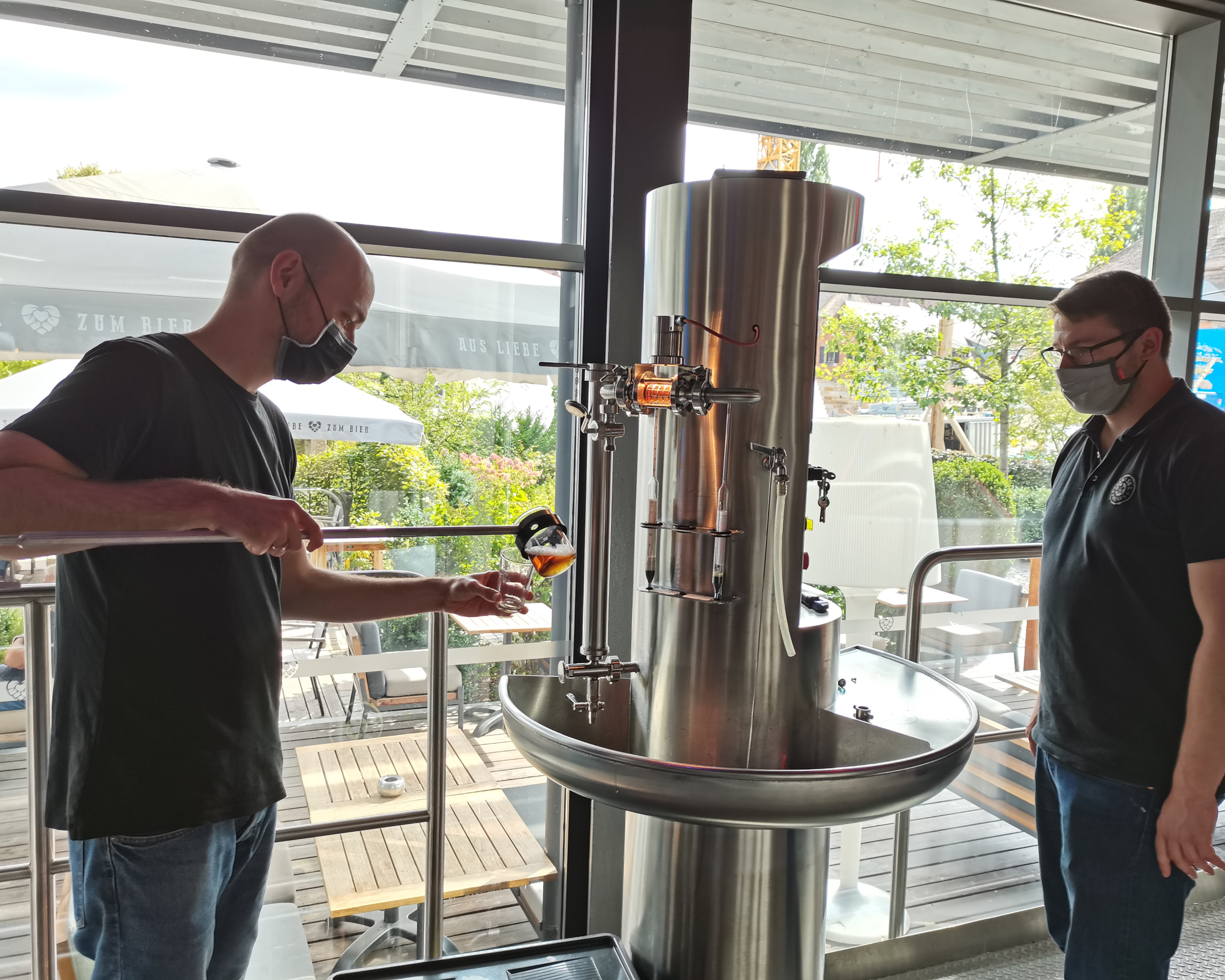 Christoph Wolfrum and master brewer Markus Briemle take a wort sample in the brewhouse