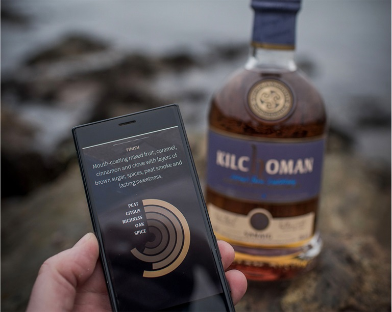 Cell phone with an app on the screen in one hand and a whisky bottle behind it