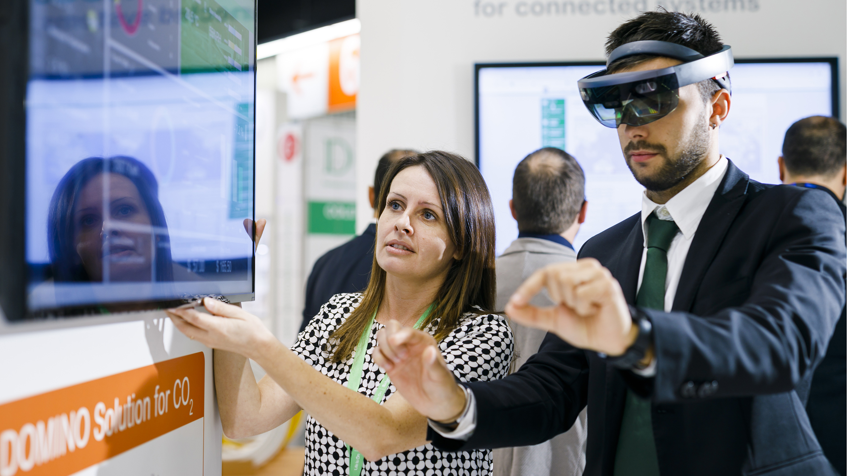 Woman looking at a screen. Man wears VR glasses.
