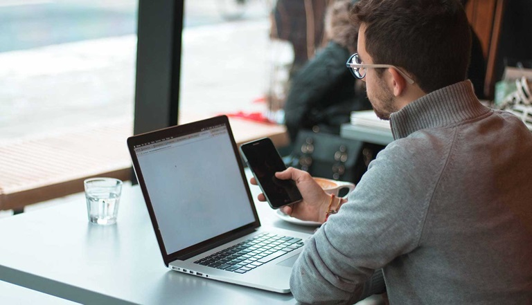 Man with smartphone in front of notebook