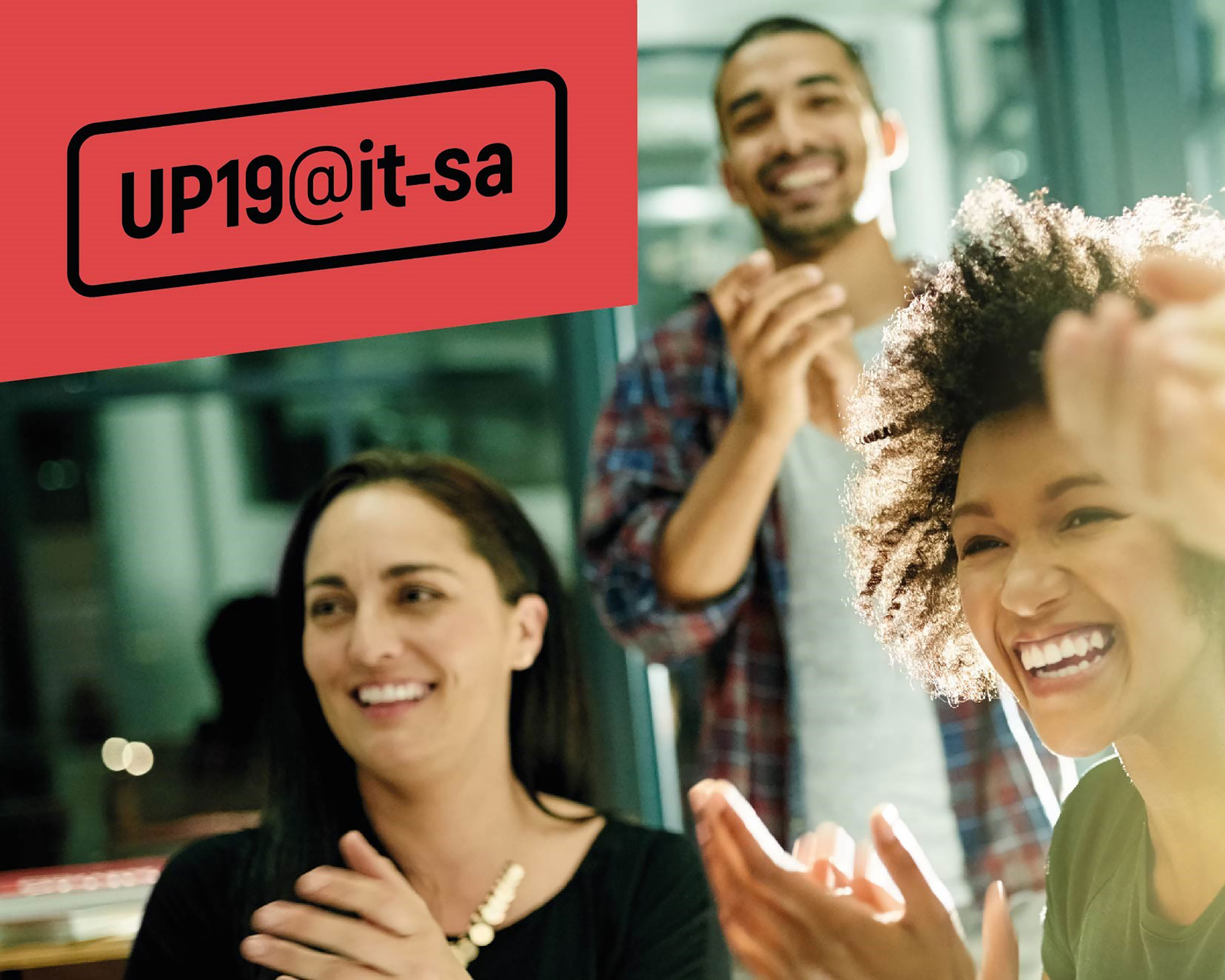Two young women and a young man are smiling and applauding; in the top left corner you can see the claim UP19@it-sa