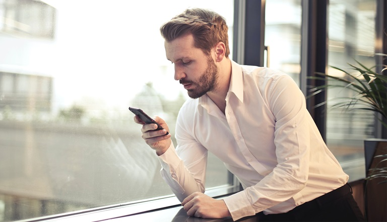 Man in a white shirt looks at his smartphone