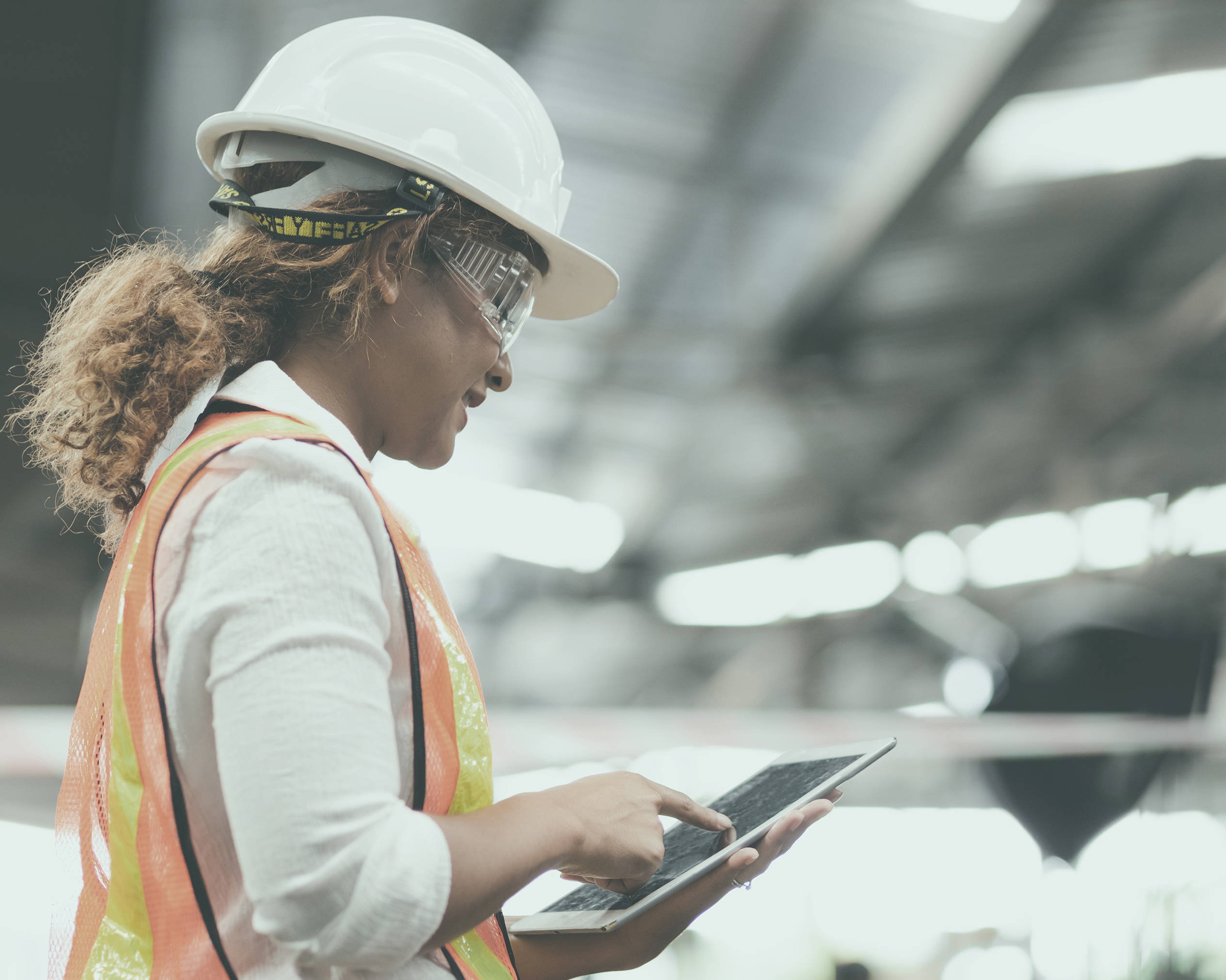 itsa 365: Woman with safety helmet typing on her tablet in her hand